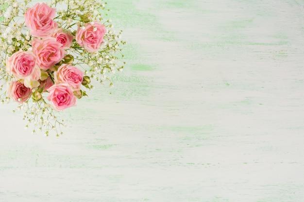 Hellrosa rosen und weiße blumen auf hellgrünem hintergrund