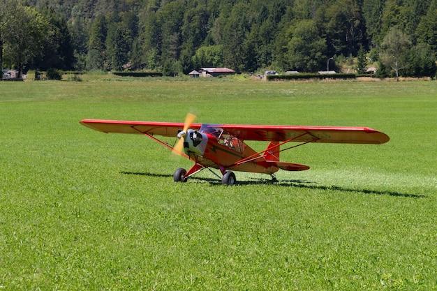Hellrote flugzeuglandung auf einer grünen wiese, transport, im freien