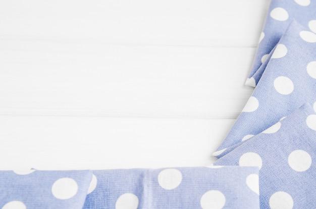 Hellviolettblaue tupfen gefaltete tischdecke über gebleichtem holztisch. draufsichtbild. copyspace