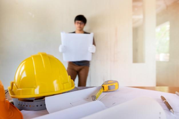 Helm und blaupause auf schreibtisch vor ingenieur oder architekt.