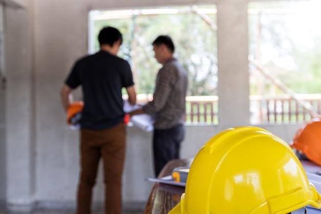 Helme auf dem schreibtisch vor dem ingenieur oder architekten, die mit vorarbeiter besprechen