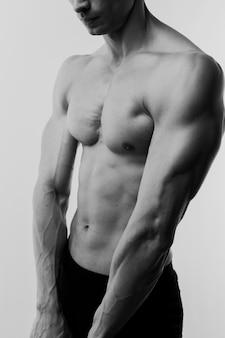 Hemdloser athletischer mann, der körper aufwirft und vorführt