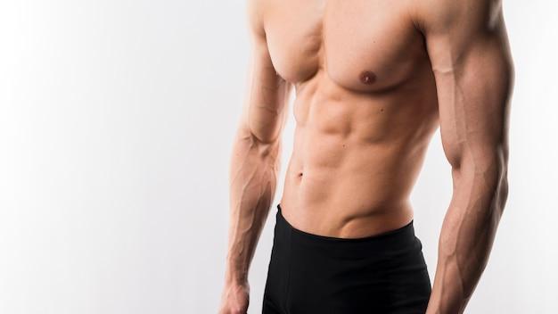 Hemdloser athletischer mann, der körpermuskulatur vorführt