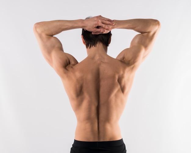 Hemdloser athletischer mann, der rückenmuskulatur vorführt