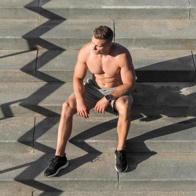 Hemdloser athletischer mann der vorderansicht, der auf treppen sitzt