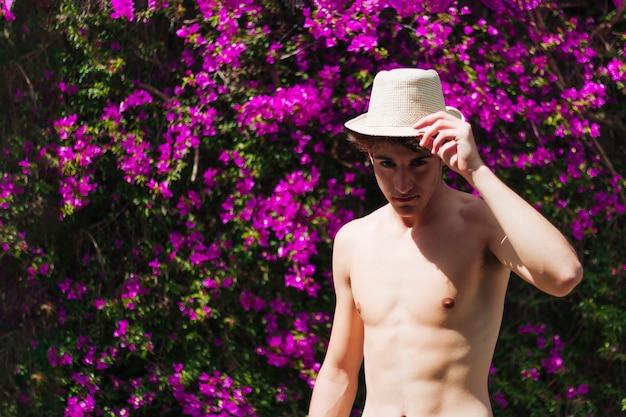 Hemdloser gutaussehender mann, der hut bei stehendem blumenbaum an draußen hält