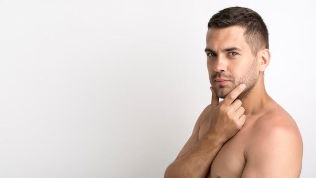 Hemdloser junger mann, der gegen weißen hintergrund aufwirft