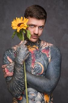 Hemdloser junger mann mit tätowierung auf seiner karosserie, die in der hand sonnenblume gegen grauen hintergrund hält