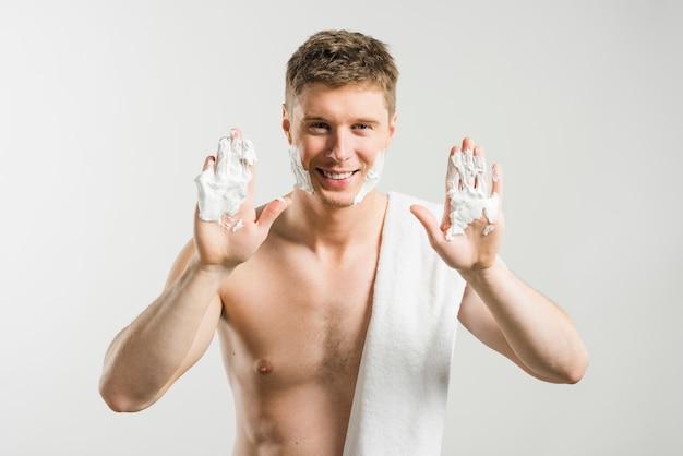 Hemdloser lächelnder junger mann, der schaum auf seinen palmen gegen grauen hintergrund rasierend darstellt