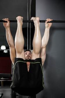 Hemdloser mann, den das handeln an der crossfit turnhalle hochzieht