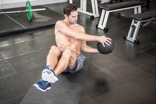 Hemdloser mann, der mit medizinball an der turnhalle trainiert