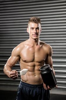 Hemdloser mann, der proteinpulver an der turnhalle hält