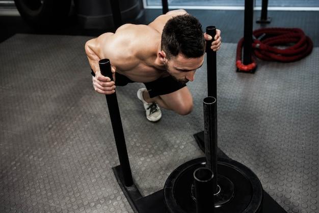Hemdloser mann, der schwere gewichte an der crossfit turnhalle drückt