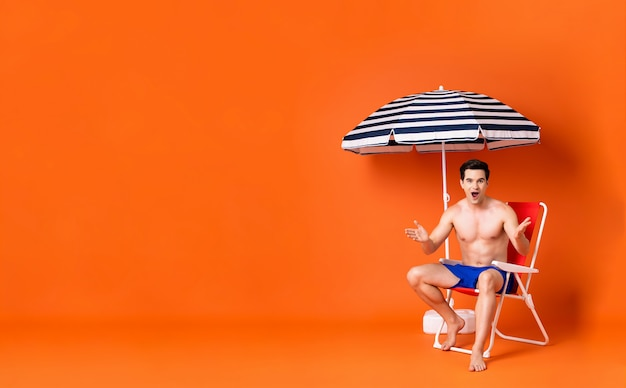 Hemdloser mann in den armen hob die entsetzte geste an, die auf strandstuhl sitzt