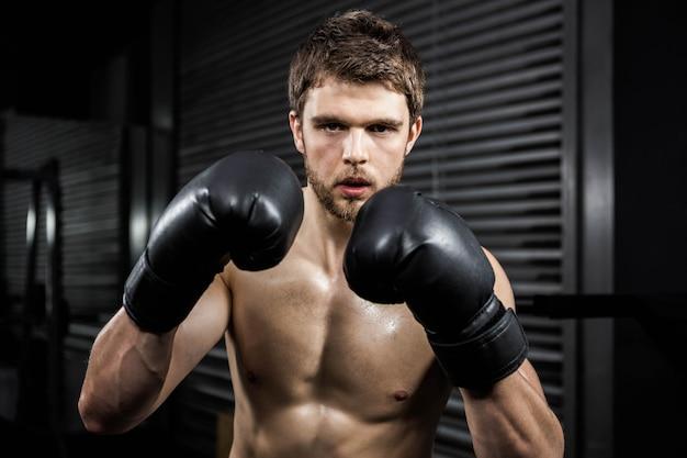 Hemdloser mann mit boxhandschuhen an der crossfit turnhalle