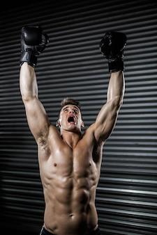 Hemdloser mann mit boxhandschuhen zujubelnd an der crossfit turnhalle