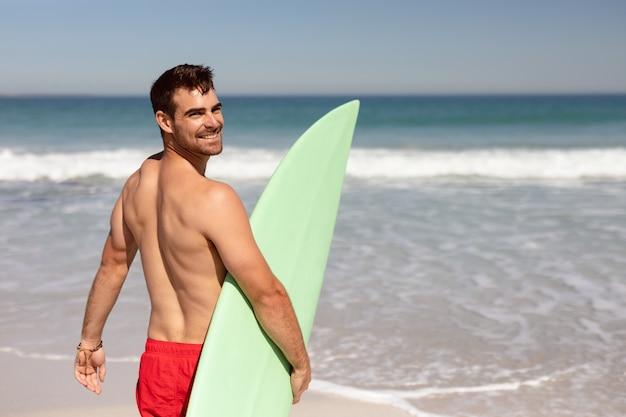 Hemdloser mann mit dem surfbrett, das kamera auf strand im sonnenschein betrachtet