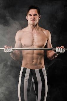 Hemdloser mann mit muskeln, der mit rauche und gewichten aufwirft