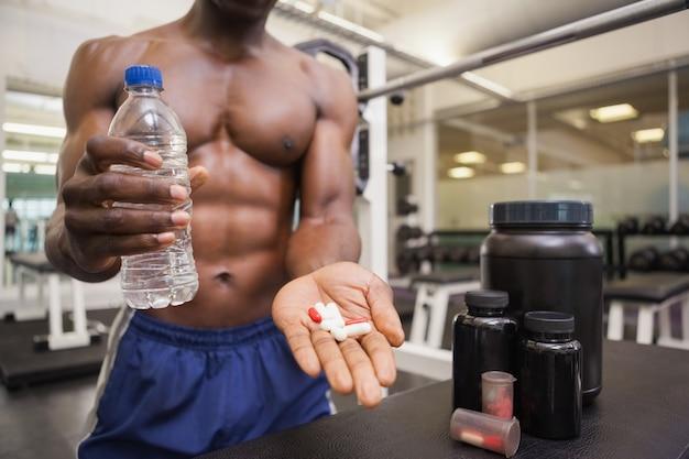 Hemdloser muskulöser mann, der vitaminpillen hält