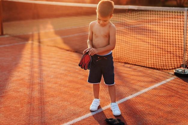 Hemdloser sportlicher junge, der die handschuhe des torhüters anzieht, während er morgens im sommer auf dem spielplatz steht.