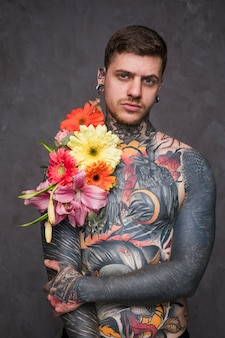 Hemdloser tätowierter junger mann des hippies mit blume auf seinem körper und durchbohren in seinen ohren und in nase, die kamera betrachten
