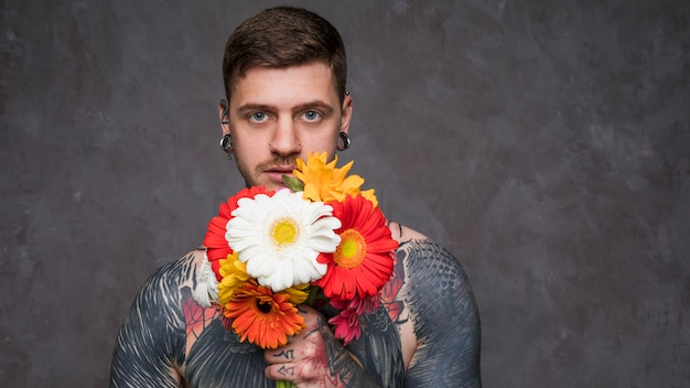 Hemdloser tätowierter junger mann mit den durchbohrten ohren, die in der hand bunte gerberablume halten