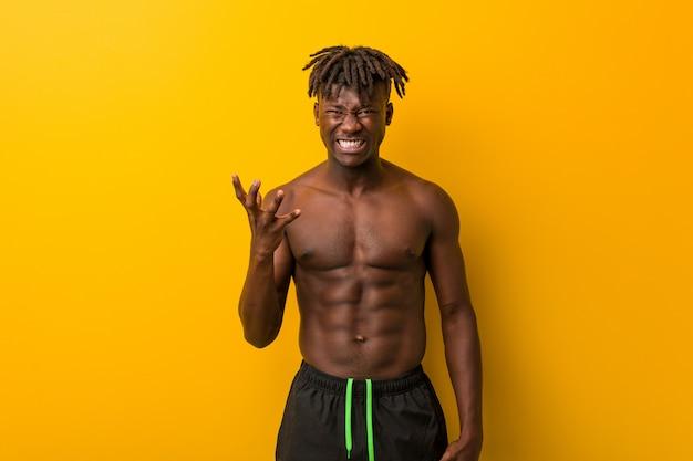 Hemdloser tragender badeanzug des jungen schwarzen mannes, der mit raserei schreit.