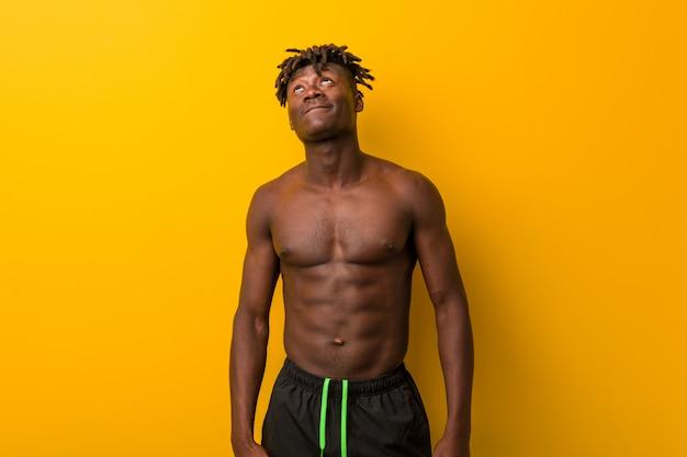 Hemdloser tragender badeanzug des jungen schwarzen mannes, der vom erreichen von zielen und von zwecken träumt