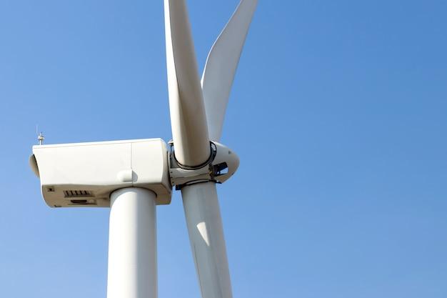 Herauf die windkraftanlage geschlossen, die strom auf blauem himmel mit clounds, windmühlen für ökologiekonzept des stroms erzeugt