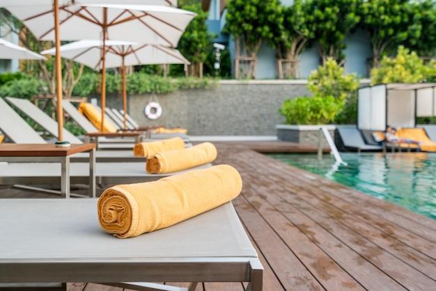Herauf orange tuch auf einem sonnenruhesesselhintergrund des pools im erholungsort oder im hotel aufgerollt.