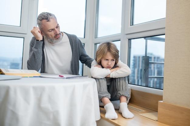 Heraufholen des prozesses. grauhaariger bärtiger mann, der mit seinem kind spricht, während er launisch aussieht looking