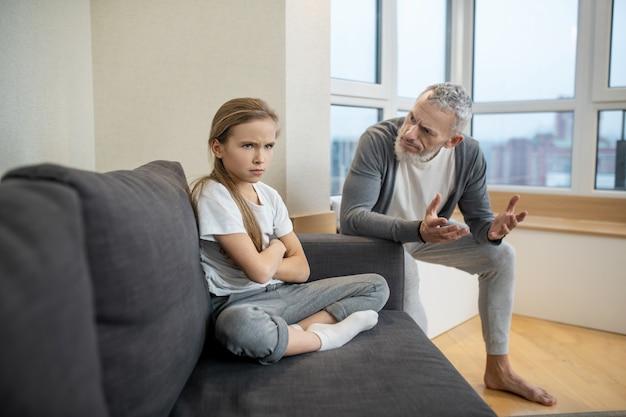 Heraufholen des prozesses. grauhaariger bärtiger mann, der mit seinem kind spricht, während sie launisch aussieht looking