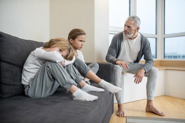 Heraufholen des prozesses. grauhaariger bärtiger mann, der mit seinen kindern spricht, während sie launisch aussehen looking