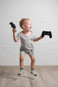 Herausgenommener junge, der steuerknüppel springt und hält