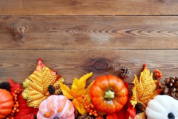 Herbst, abstrakte rahmenkomposition des herbstes mit bunten blättern, tannenzapfen und kürbissen auf holzhintergrund, kopienraum für text