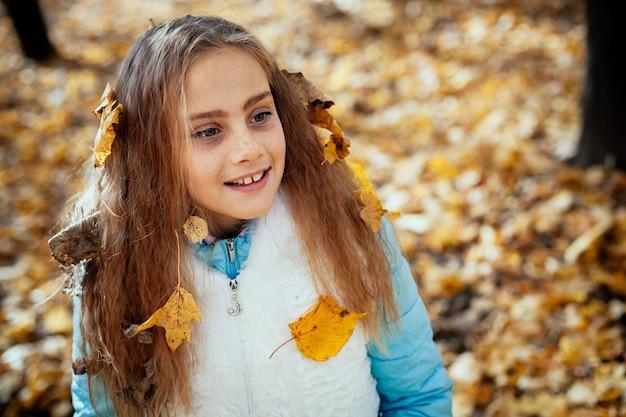 Herbst-außenporträt des schönen glücklichen kindermädchens, das im park in der warmen kleidung geht