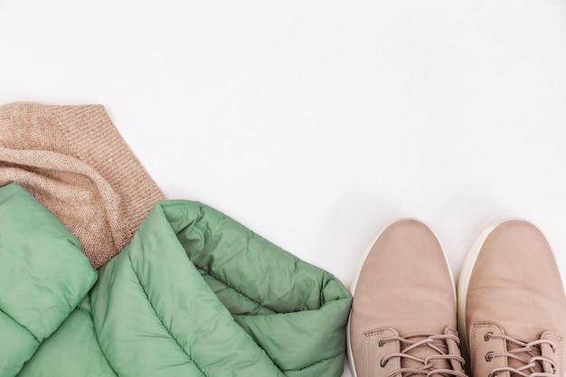 Herbst bequeme kleidung. trendige warme daunenjacke in minze, leichte lederstiefel und strickschal. weibliche kleidung. fashion-konzept. flach liegen. ansicht von oben.