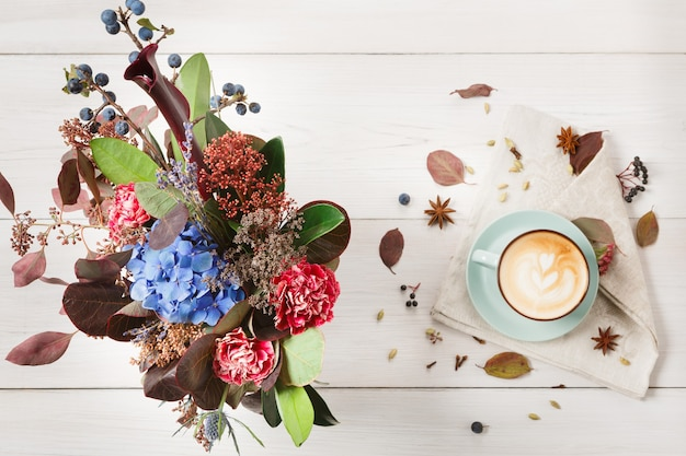 Herbst cappuccino zusammensetzung. blaue kaffeetasse draufsicht mit schaum, nelken, getrockneten blumenstrauß am weißen holztisch. herbst heiße getränke, café und bar konzept