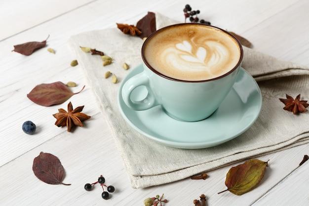 Herbst cappuccino zusammensetzung. blaue kaffeetasse mit schaum, nelken, herbstblumen am weißen holztisch. herbst heiße getränke, café und bar konzept