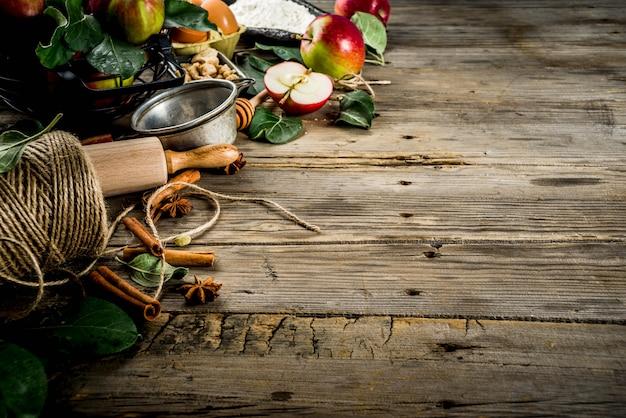 Herbst, der hintergrund, apfelkuchenbackenkonzept, frische rote äpfel, süße gewürze, zucker, mehl kocht