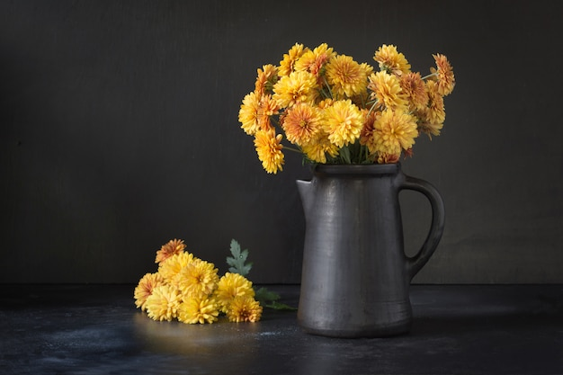Herbst dunkles stillleben. fallen sie mit gelben chrysanthemenblumen im tonwarenvase auf schwarzem.