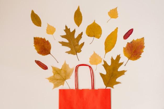Herbst einkaufen mit rabatten. herbstverkauf. eine rote papiereinkaufstasche mit den herbstgelbblättern, die aus ihr heraus spähen.