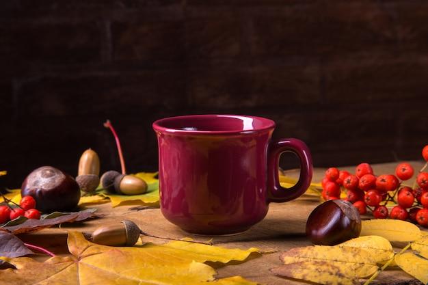 Herbst, fallblätter, heißer dämpfender tasse kaffee auf holztischsonntagmorgenkaffee entspannend und stilllebenkonzept.