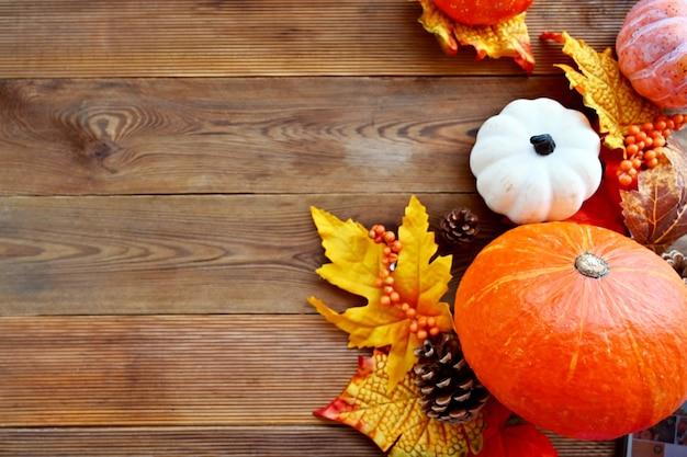 Herbst, fallen abstrakte rahmenkomposition mit bunten blättern, tannenzapfen und kürbissen auf holzhintergrund, kopienraum.