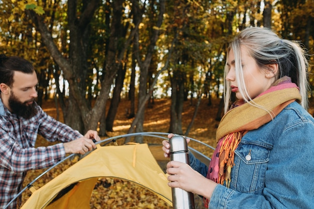 Herbst familienreise. paar hielt im naturpark an. mann, der zelt aufbaut, dame, die mit thermoskanne steht.