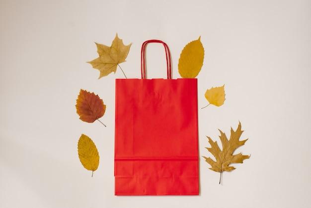 Herbst flach legen eine handgemachte rote tasche und herbstlaub nebeneinander auf hellem hintergrund