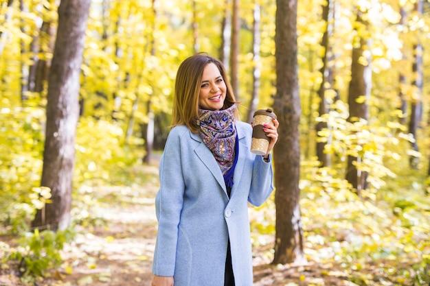 Herbst-, getränke- und personenkonzept - frau, die tasse heißes getränk hält