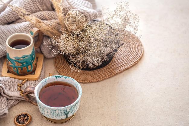 Herbst hauskomposition mit einer schönen keramik tasse tee auf dem tisch. dekorationsgegenstände im innenraum.