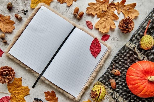Herbst-, herbst- oder halloween-komposition aus getrockneten blättern, kürbis, tannenzapfen, eicheln, warmem schal und hand mit tasse kaffee auf konkretem hintergrund. leeres notizbuch des vorlagenmodells mit kopienraum.