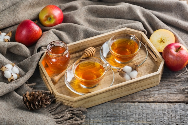 Herbst, herbst, winter wohnkultur im hygge-stil mit getränk. saisonale komposition mit tasse heißem tee mit honig, warmem wollschal, weichem plaid auf einem rustikalen holztisch.
